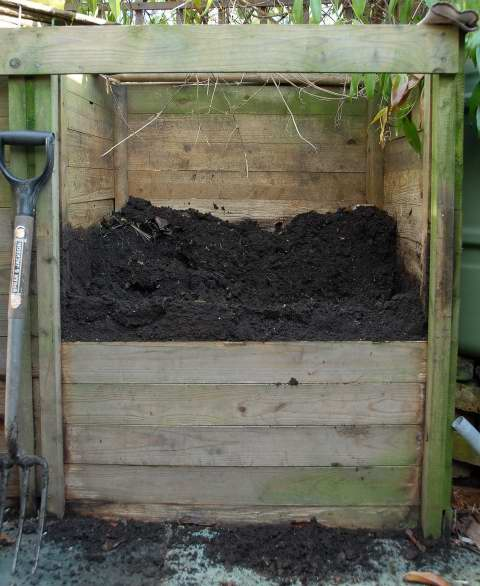 Wooden compost bin full of mature compost.