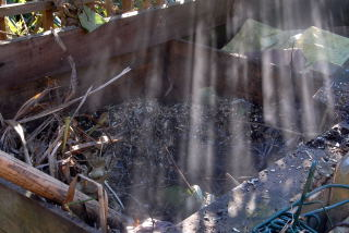 Steam rising from a recently filled compost heap.